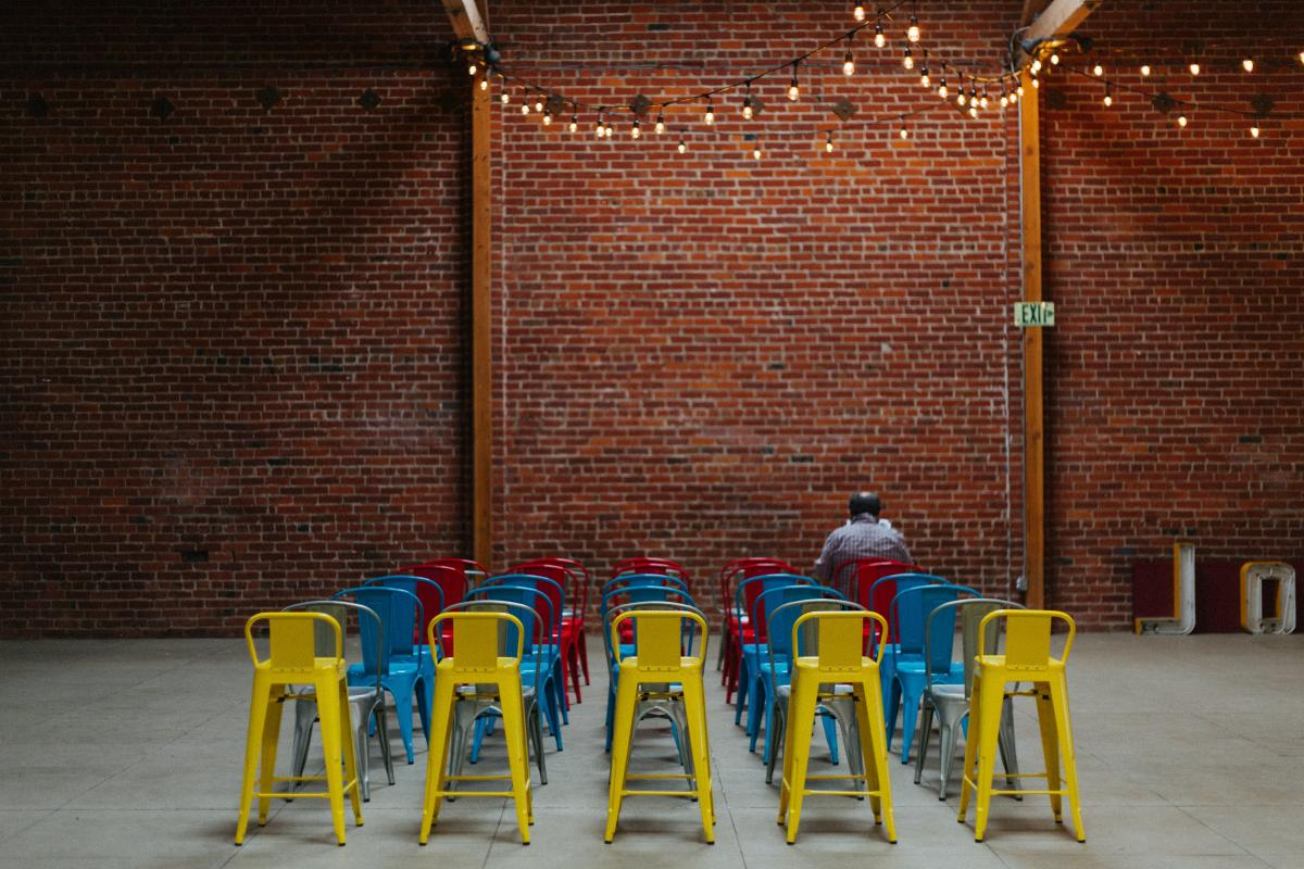 rows of colourful chairs in front of brick wall